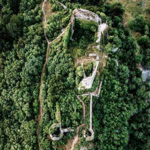 """The remains of Old Vipava Castle  from above.   It was around 1100 when the Counts of Bogen built the castle – also referred to as the """"Upper Castle"""" – on an elevation over the village of Vipava, on the slopes of Mt. Nanos. But the hill has also shown signs of prehistoric settlement. The castle was ruled by many families, including one Baron Herberstein. In 1486 his son, Sigismund von Herberstein, a noted Habsburg diplomat and the ambassador of the Holy Roman Empire to Russia, was born here and also spent his childhood. In the tumultuous 15th century, when Vipava was frequently ravaged by Ottoman incursions, the castle was fortified. In 1528 it passed to the Lanthieri family. However, the family preferred to live in the Lower Castle and the less accessible Upper Castle was abandoned sometime in the late 16th century. A footpath leads up to the weathered ruins of the Old Castle, offering a lovely view of the Vipava Valley    #ifeelsLOVEnia #mojaslovenija #sloveniaculture  Photo by @irenaudovic."""