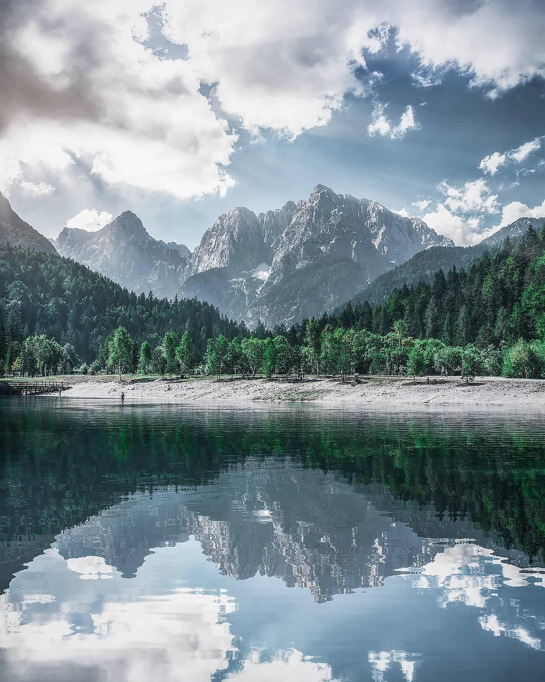 LAKE JASNA   What a reflection of these majestic mountains!  Anyone up for a short break at the Jasna Lake?  It consists of two interconnected artificial lakes at the confluence of the Velika Pišnica a and Mala Pišnica streams. Thanks @mandrake80 for sharing your photo with #ifeelsLOVEnia.