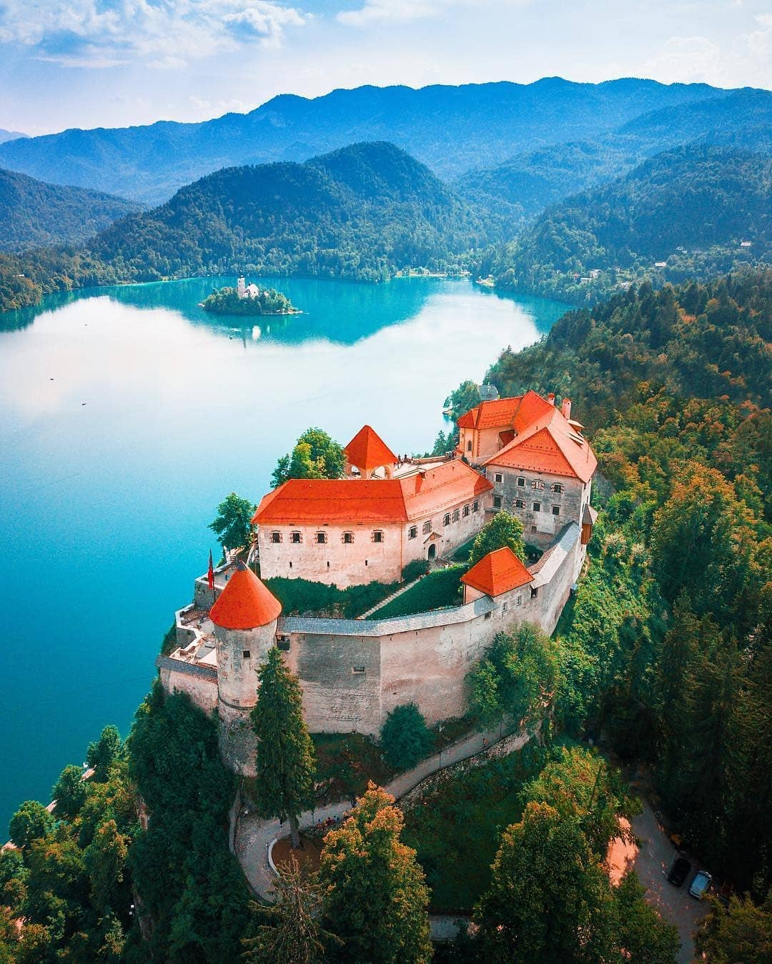 Different perspective on lake Bled from hot air baloon. Mighty Bled castle in front with legendary island in the background.   Thanks @mblockk for sharing your photo with #ifeelsLOVEnia.
